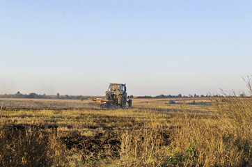 Tractor cultivating wheat stubble field with crop residue