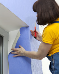 Woman cutting length of wallpaper