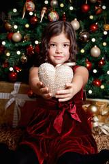 Happy little girl holding a heart