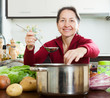 Smiling mature woman adding seasoning into  soup pan