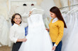 Shop assistant  helps the bride in choosing bridal gown