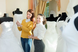bride chooses bridal outfit at wedding store