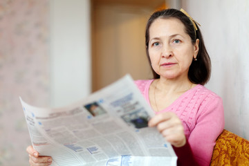 serious woman reading newspaper