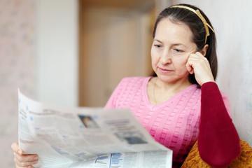 pensive woman reading newspaper