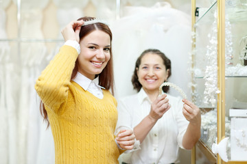 Shop assistant  helps the bride in choosing bridal diadem