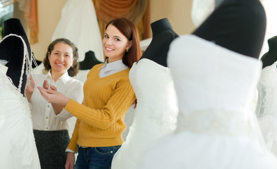 assistant  helps to girl chooses white bridal outfit