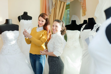 bride chooses bridal outfit at wedding store