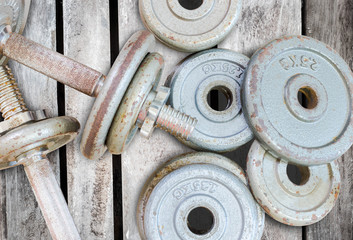 Fitness equipment dumbbell weights on old wood background
