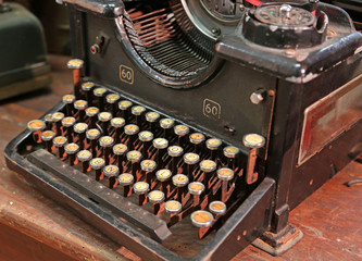 vintage black rusty typewriter with white keys