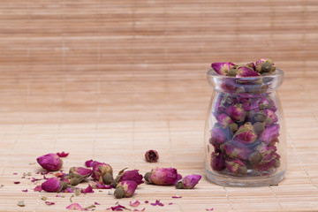Dried roses, wooden scoop of rose tea on bamboo mat