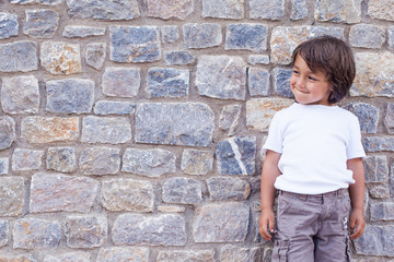 little kid on a stone wall