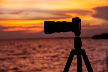 Camera silhouetted against the sea.