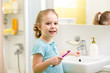 Smiling child brushing teeth in bathroom