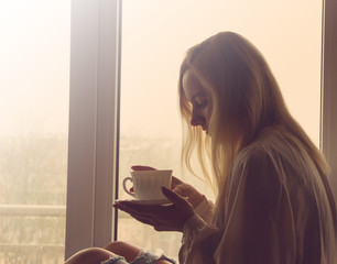 woman drinking coffee in the morning sitting by the window.