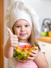 little girl preparing healthy food and showing thumb up