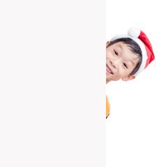 Smiling Christmas little boy in red  hat peeking from blank boar