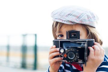 little boy using a vintage camera