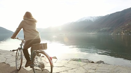 Woman riding a bicycle by the edge of the lake