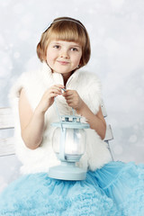 Little girl sitting on the bench with lantern