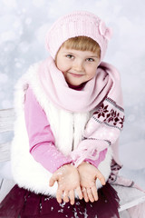 Pretty little girl with snow in her hands
