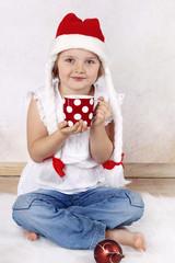 Girl in Santa's hat drinking cocoa