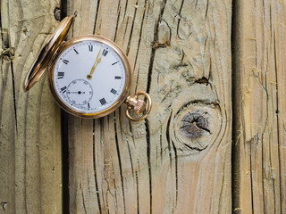 gold pocket watch against  aged wood