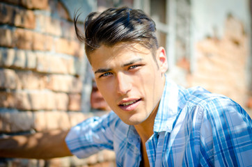 Attractive young man outdoors smiling and looking in camera,