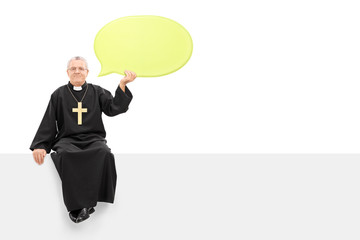 Mature priest holding a speech bubble seated on panel