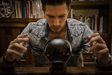 Male seer predicting future by looking into crystal ball