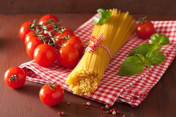 raw spaghetti pasta basill tomatoes. italian cuisine in rustic k