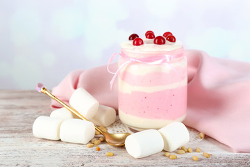 Raspberry milk dessert in glass jar,