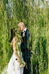Sposi si baciano sotto glicine