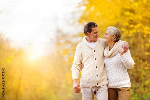 Active seniors walk in nature - 73778914