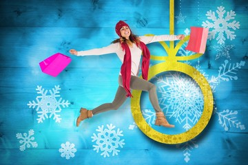 Composite image of smiling brunette jumping with gifts bags