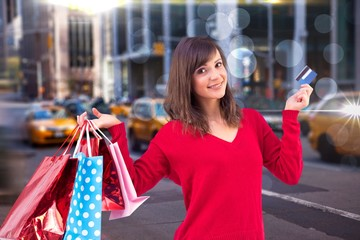 Composite image of brunette holding gift and credit card