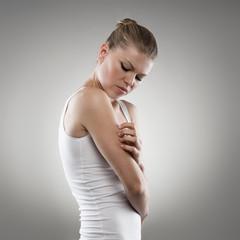 Young female scratching her rash arm. Woman having eczema pain