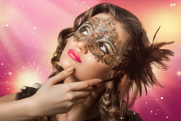 Beauty shoot of smart brunette woman in carnival mask over color