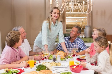 Woman serving christmas dinner to her family