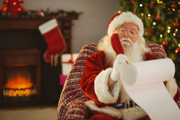 Concentrated santa writing his list on a scroll