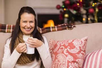 Smiling brunette enjoying hot chocolate