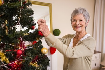 Senior woman decorating the christmas tree