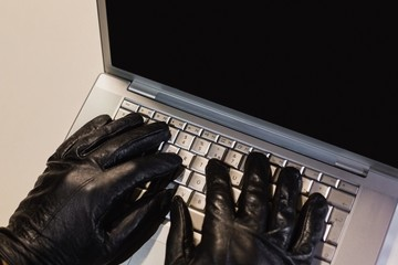 Close up of burglar hacking a laptop