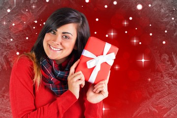 Composite image of excited brunette holding red gift