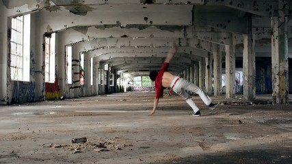 Young boy dancing breakdance in the old hall