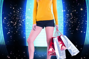Composite image of stylish woman with shopping bags