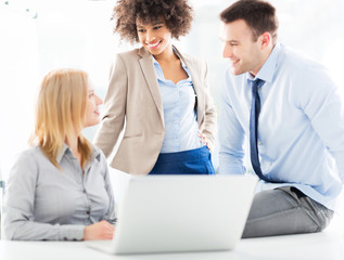 Business colleagues using laptop together