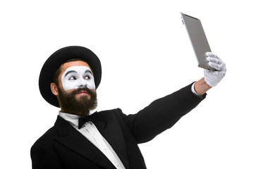 Man with a face mime looks in the laptop as mirror