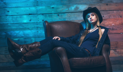 Cowgirl Wearing blue jeans and brown hat. Sitting on leather cha