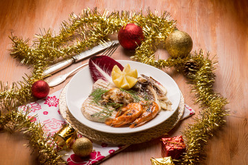 mixed grilled fish with red chicory over christmas table