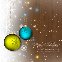 Christmas bauble on wooden background with snowflakes